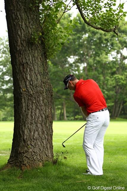 ブレンダンにも不運が・・・9番ティショットは木の根っこ。左打ちで脱出。