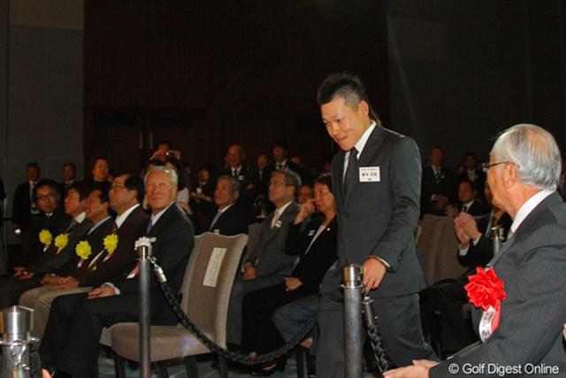 新人賞の藤本佳則は、安西JGA会長(手前)や永久シード5人の前を会釈しながら登壇