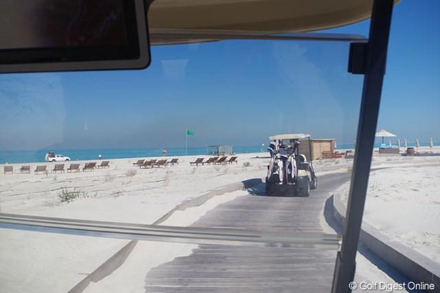 2013年 アブダビHSBCゴルフ選手権 サディヤットビーチGC カートは、海水浴を楽しむ人々の横を通り抜けていく