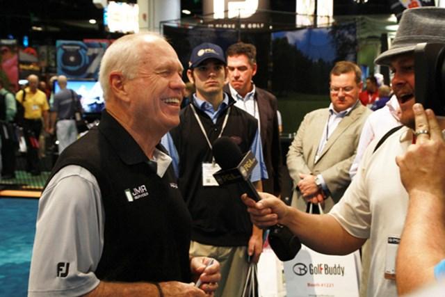 ブッチ・ハーモン=ウィングリップのブースでTVのインタビューに笑顔で答えるハーモン。ずいぶんダイエットしました
