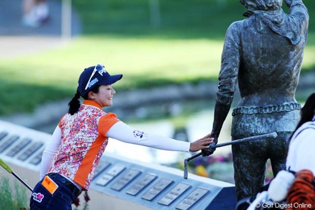 2013年 クラフトナビスコ選手権 事前 上原彩子 18番グリーン脇に立つダイナ・ショアの銅像に触れて、ゲン担ぎする上原彩子