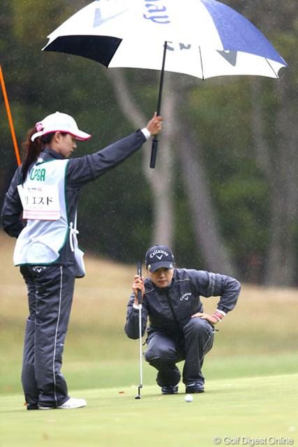 傘でボールを濡らさないようにするのもキャディさんの仕事です