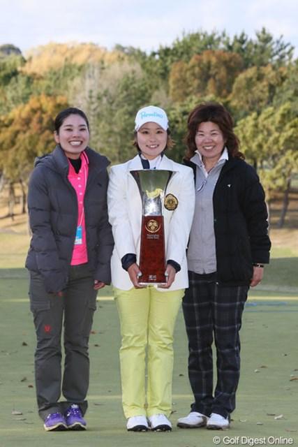 2013年 ヤマハレディースオープン葛城 最終日 姉・久美子さん、比嘉真美子、母・彰子さん 母の彰子さん(右)と姉の久美子さん(左)と記念写真に収まる比嘉真美子。「家族みんなで勝ち獲った勝利です」