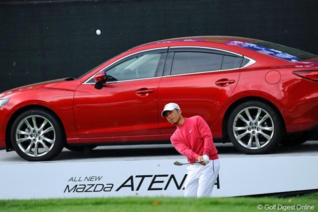 2013年 つるやオープンゴルフトーナメント 2日目 原口鉄也 優勝副賞のATENZAの前でアプローチショット。5バーディ、2ボギーと2日連続で68をマークして8位タイの好位置キープ。