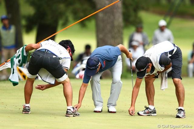 2013年 ダイヤモンドカップゴルフ 3日目 谷口徹 15番グリーンで松の実?拾い、3人の姿勢がおなじでちょっと面白い光景