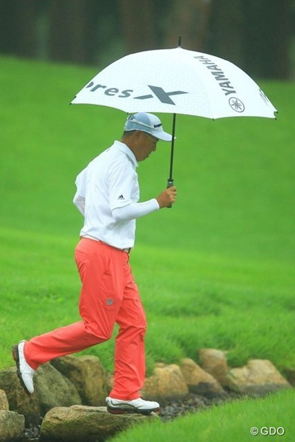 一日を通して霧雨が続いた初日。谷口徹はレインパンツで傘をさし雨対策はバッチリOK