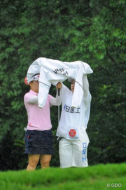 2013年 日医工女子オープンゴルフトーナメント 最終日 井芹美保子 なんせ突然に降り出すもんやから傘も間に合いませんねん・・・。急場をしのぎのカッパを広げて雨宿り・・・。この直後に2度目の中断となります。