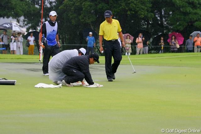 グリーン上に溜まった水を競技委員がタオルで吸い取り応急処置