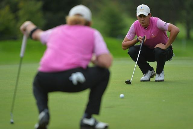 49歳のヒメネス(背中)と協力してラインを読む20歳のマナッセロ。ゴルフの団体戦ならではの光景(Stuart Franklin/Getty Images)