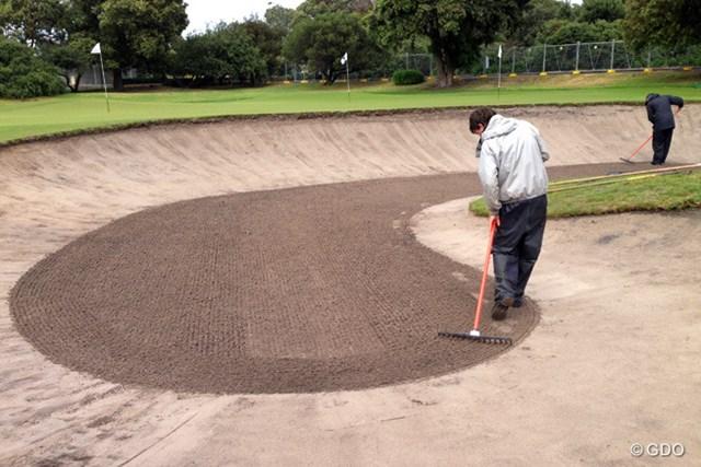 """2013年 ISPSハンダワールドカップ 3日目 練習場のバンカー整備 朝の練習用バンカー。砂を整えたあとクワで""""年輪""""を描いてできあがり"""