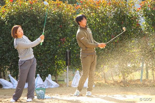 土の上からアプローチ練習をする石川。手前は大江香織