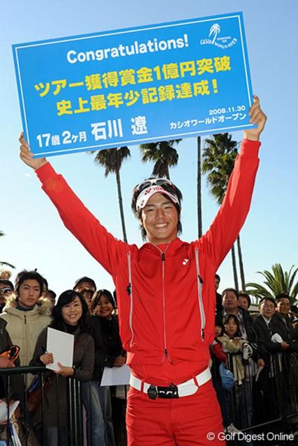 獲得賞金1億円突破に記念プレートを掲げる石川遼(代表撮影)