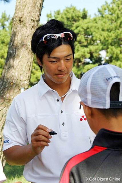 日本オープンの会場で子供にサインをする石川遼