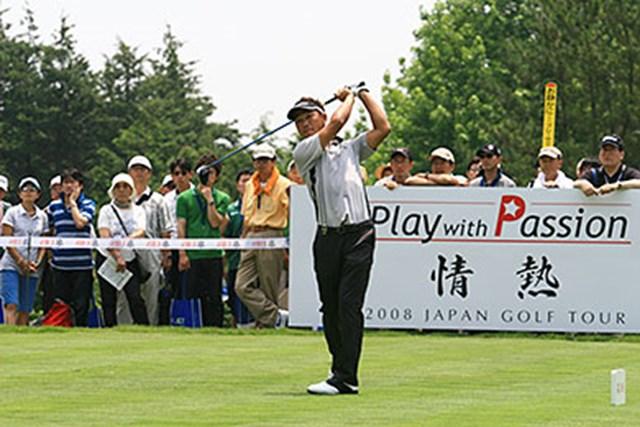 今季のジャパンゴルフツアーが掲げるスローガンの看板の前で、飄々とティショット!